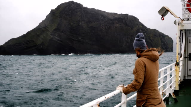 Young beautiful woman standing on the board of ship in sea. Traveling female exploring Iceland alone in overcast weather