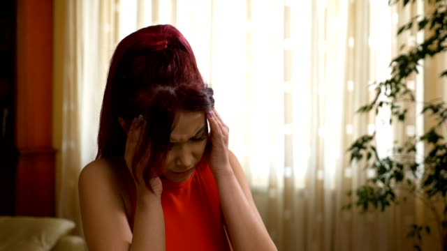 Young beautiful woman suffering from headache rubbing hands against temples video