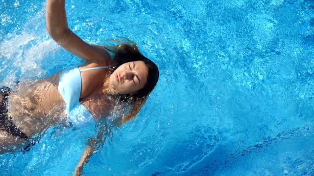 young beautiful woman swimming on the back at the pool. tanned girl floating at the basin of hotel and relaxing on sunny day. summer vacation or holiday concept. close up slow motion top view - ritemprarsi video stock e b–roll