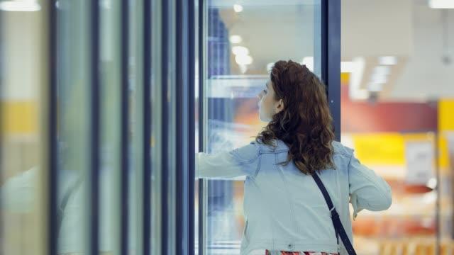 junge, schöne frau nimmt gefrorenes gemüse aus einer gekühlten supermarkt-vitrine. kamera-verkabelung. - gefrierkost stock-videos und b-roll-filmmaterial