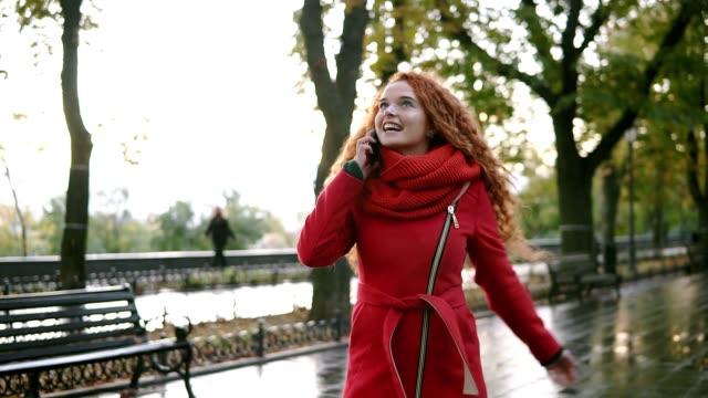vídeos y material grabado en eventos de stock de mujer hermosa joven hablando por su teléfono móvil sobre un fondo. emocionada, feliz rojo rizada pelo chica caminando en el parque otoño, girando en disfrute. mujer en capa roja con su smartphone. mujer caminando y hablando emocionalmente - moda de otoño