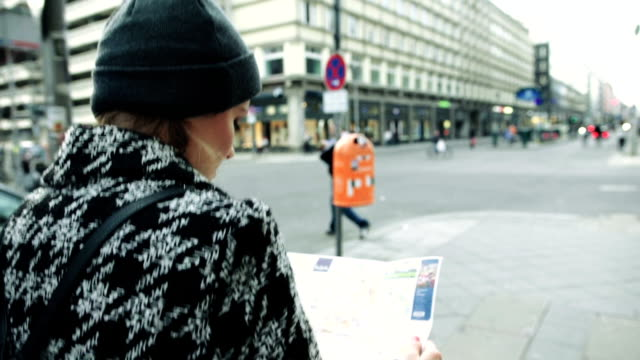 Young beautiful woman travelling with a map in the city. video