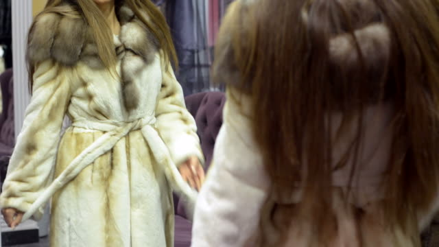 young beautiful woman tries on clothes at the mall. - päls textil bildbanksvideor och videomaterial från bakom kulisserna