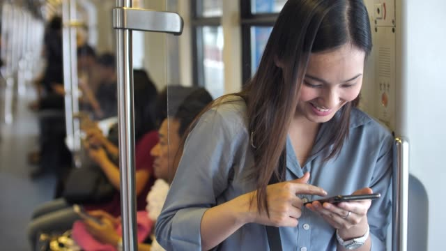 Young beautiful woman uses the smartphone in public transportation video
