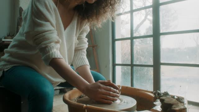 vídeos de stock, filmes e b-roll de jovem mulher bonita usando a roda de oleiro no atelier - cerâmica artesanato