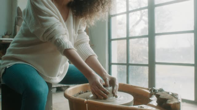 Young beautiful woman using pottery wheel at atelier video