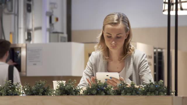 ung, vacker kvinna med surfplatta och dricka te i caféet - bordsjordglob bildbanksvideor och videomaterial från bakom kulisserna