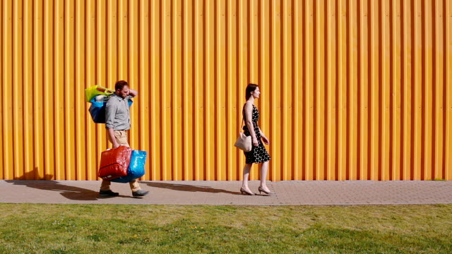 Young beautiful woman walking happily after shopping on a sunny day. Men follows her hardly carrying her bags video