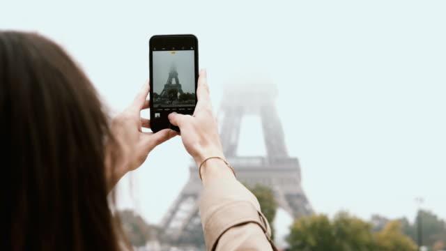 vidéos et rushes de belle jeune femme marche dans paris, france et prendre des photos de la tour eiffel dans le brouillard sur smartphone ou téléphone mobile - tour eiffel
