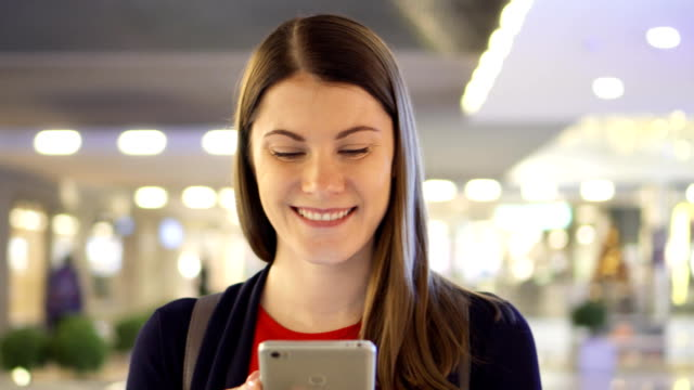 vídeos de stock e filmes b-roll de young beautiful woman walking in shopping mall smiling. using her smartphone, talking with friends - online shopping