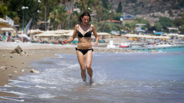 A young beautiful woman wearing black bikini running at a beach and laughing video