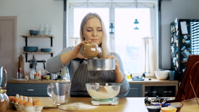 Young beautiful woman weighs the cocoa, adds to flour. Girl using kitchen scales, bowl and sieve for this video