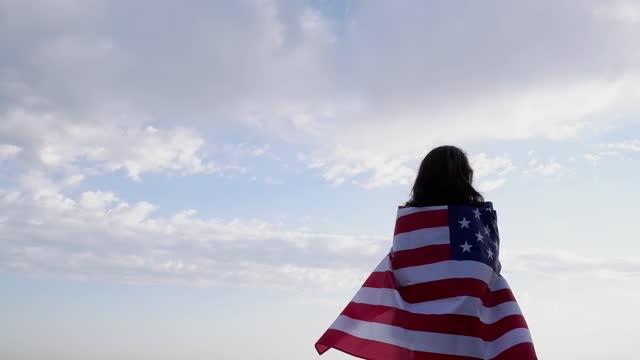 vídeos y material grabado en eventos de stock de joven hermosa mujer con el pelo negro sosteniendo una bandera de ee.uu. sobre un fondo de cielo azul con nubes. día de la independencia. - independence day
