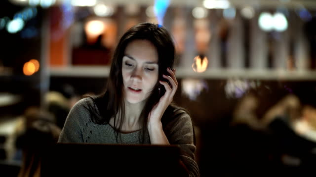 Young beautiful woman working on laptop in evening. Brunette female sitting in cafe and talking on smartphone video