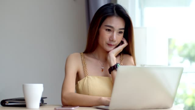 Young beautiful woman working with laptop at coffee shop