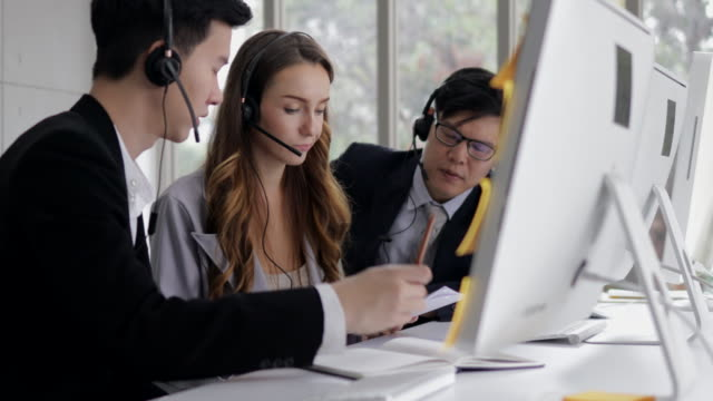 young beautiful women call center wear headset brainstorming with co-worker while consulting customer with online problem. operator service business representative concept. online marketing.
