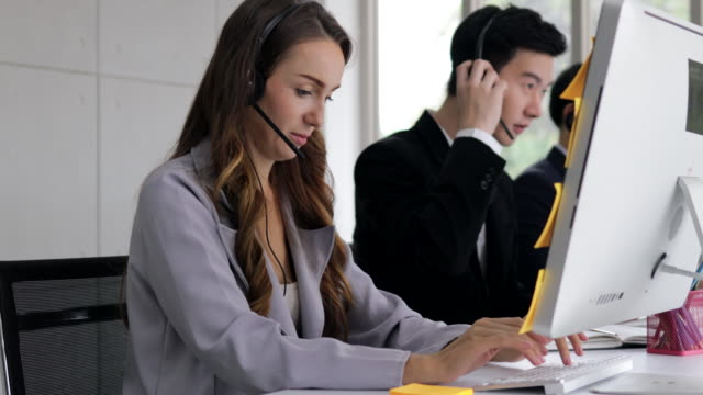 young beautiful women call center wear headset talking with co-worker while consulting customer with online problem. operator service business representative concept. online marketing.