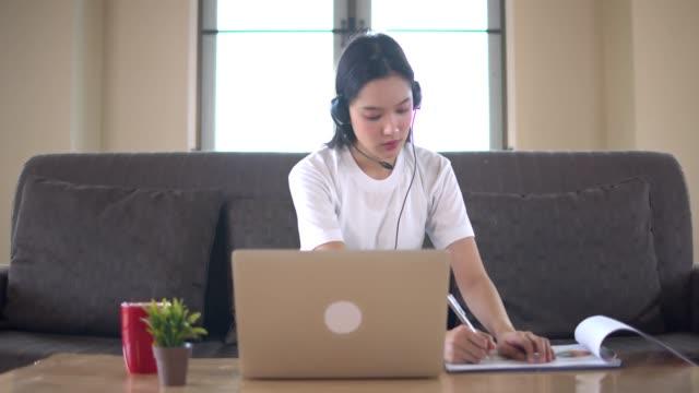giovane bella donna asiatica che impara online a casa con taccuino o tablet sedersi sul divano marrone.quarantena quando covid-19 si diffonde e l'università chiude. - esame università video stock e b–roll