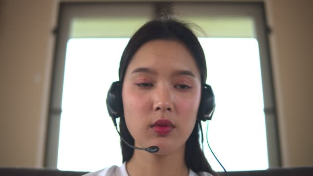 ノートやタブレットで自宅でオンラインで学ぶ若い美しいアジアの女性は、居心地の良い-19が広がり、大学が閉じるとき、茶色のソファ.quarantineに座っています。 - 人里離れた点の映像素材/bロール