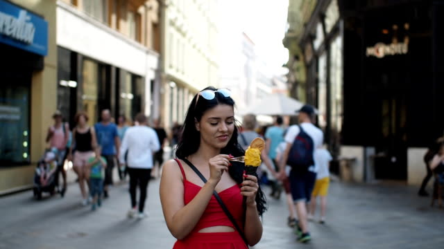 Young beauty woman smiling and eating ice cream - SLOW MOTION Young beauty woman in red dress is walking in the street of historical part of Bratislava city in sunny summer afternoon. She is smiling and eating yellow gelato. There is a pedestrian street, facades of buildings with windows, terraces of coffee shops and walking people in the background. Scene is illuminated by soft daylight and partially by sunlight. Low depth of field and blurred background. Half speed. ice cream stock videos & royalty-free footage
