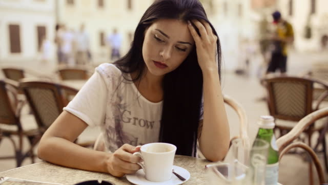 Young beauty woman waiting and drinking coffee at patio. video