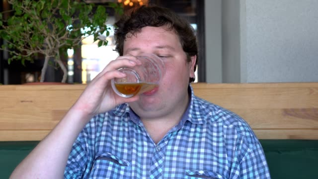 Young big man drinking a beer in cafe or pub Young big man drinking a beer in cafe or pub. plus size model stock videos & royalty-free footage