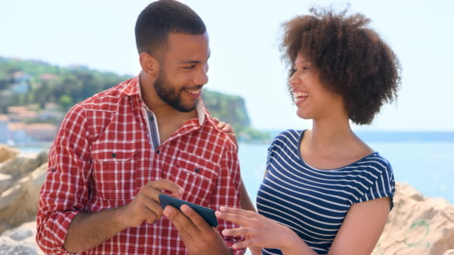 Young biracial couple checking the selfie they took on the smartphone while standing on a seaside walkway