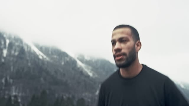 young biracial man doing his training routine by running in cold weather - maglietta video stock e b–roll