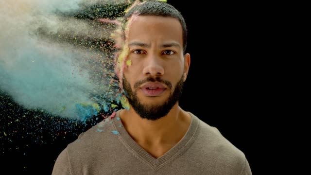 slo mo young biracial man with beard shouting while being hit with a multi colored powder - espressione del viso video stock e b–roll