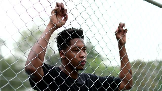ung svart afrikansk man som lutar sig mot metallstaket - etnicitet bildbanksvideor och videomaterial från bakom kulisserna