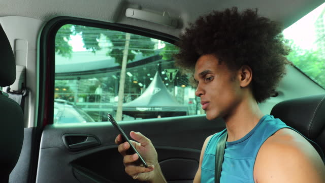 vídeos de stock e filmes b-roll de young black african man using cellphone inside car riding in the backseat of a car - phone, travelling, copy space