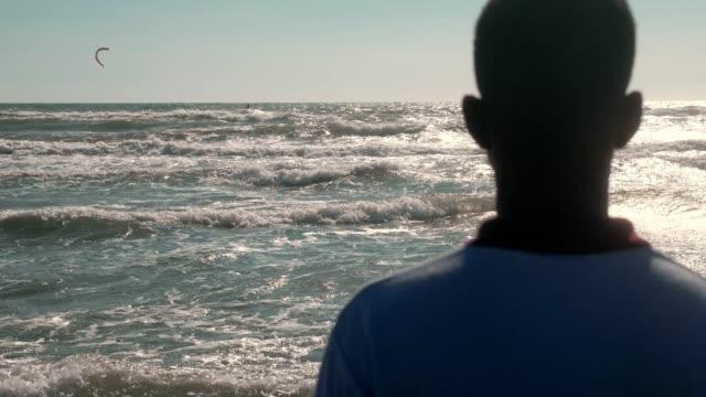 young black african migrant observing the ocean. missing home, africa, homeland - tylko jeden mężczyzna filmów i materiałów b-roll