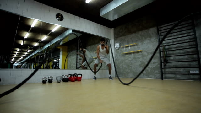 Young black athlete doing battle ropes exercise in a gym. Slow motion. video