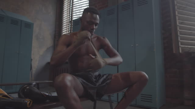 Young Black Boxer Wrapping Wrists in Dark Dingy Changing Room