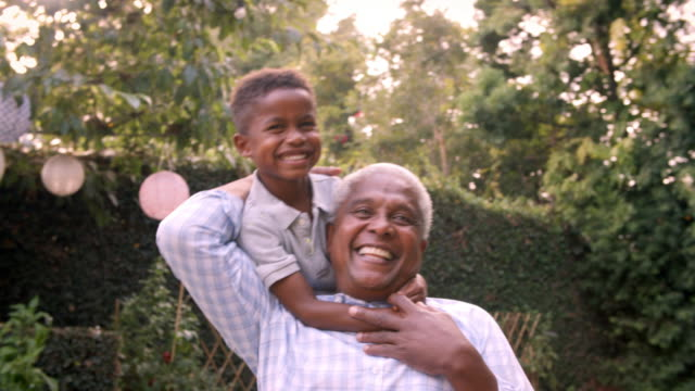 Young black boy playing with grandad in the garden, close up video