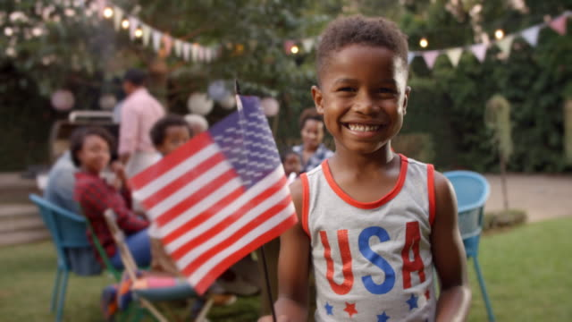 young black boy waving us flag at 4th july family barbecue - giorno dell'indipendenza video stock e b–roll