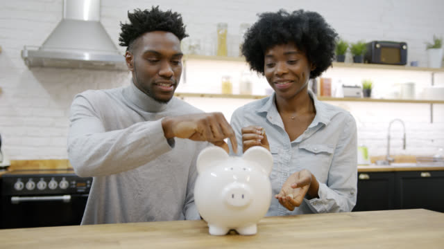 Young black couple at home laughing while insetting coins into their piggy bank Young black couple at home laughing while insetting coins into their piggy bank - Lifestyle concepts piggy bank stock videos & royalty-free footage
