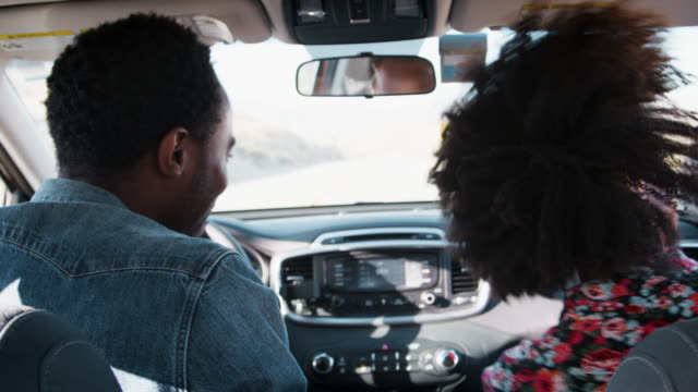 Young black couple dancing in car as they drive, back view