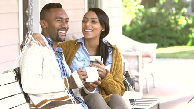 Young black couple drinking coffee on porch swing video
