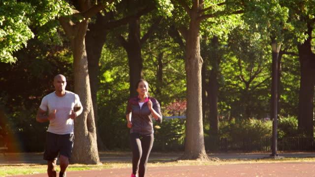 vidéos et rushes de jeune couple noir, jogging dans le parc de brooklyn - running
