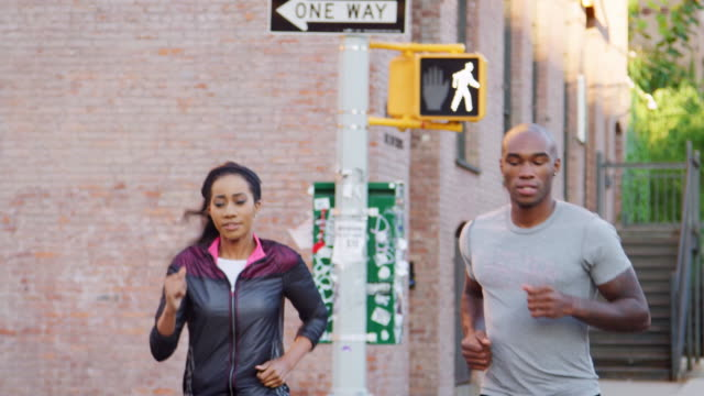 vídeos de stock e filmes b-roll de young black couple jogging in brooklyn street, close up - young woman running city