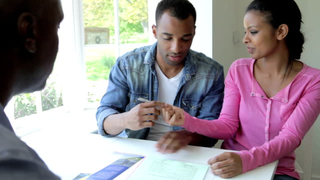 young black couple meeting with financial advisor at home - tvåföräldersfamilj bildbanksvideor och videomaterial från bakom kulisserna