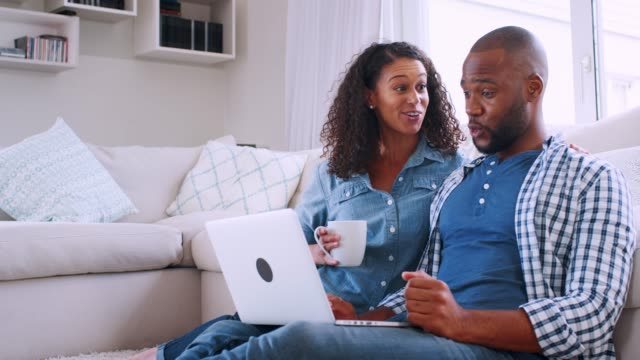 Young black couple sitting on sofa and looking at computer Young black couple sitting on sofa and looking at computer boyfriend stock videos & royalty-free footage