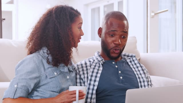 Young black couple sitting on sofa looking at computer Young black couple sitting on sofa looking at computer face to face stock videos & royalty-free footage