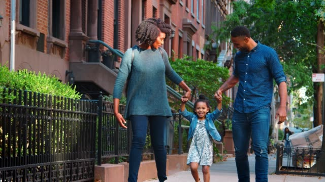 Young black couple swinging daughter as they walk in the street