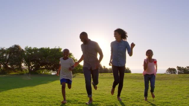 公園内移動カメラに向かって実行している若い黒家族 ビデオ