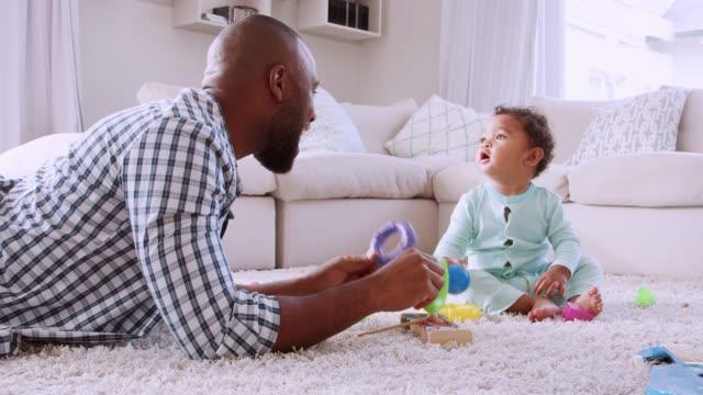 stockvideo's en b-roll-footage met jonge zwarte vader liggend op de vloer spelen met zijn jonge zoon - baby toy
