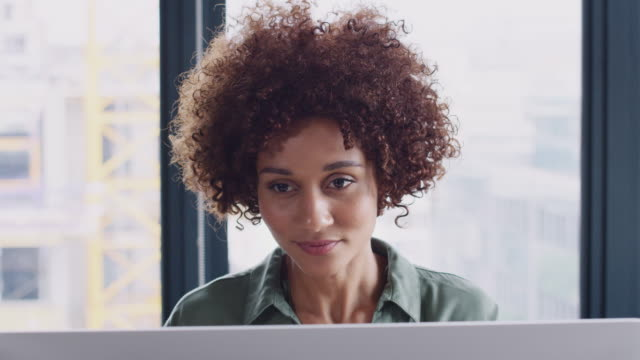 Young black female creative looking at computer monitor in an office and drinking coffee, close up