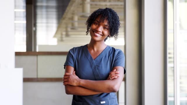 genç siyah kadın doktor önlük giyiyor - cerrahi önlük stok videoları ve detay görüntü çekimi
