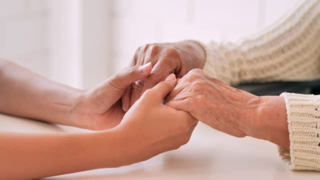 Young black female nurse doctor hold hand of senior grandmother patient help express empathy encourage tell diagnosis at medical visit at home.Medical,Healthcare,Caretaking,Senior Care,Retirement, Family,Lifestyle,Volunteer,Charity,Nursing home concept video